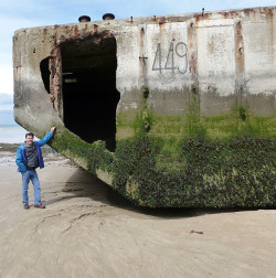 Geoff Pringle beside section of Mulberry Harbour, Arromanches
